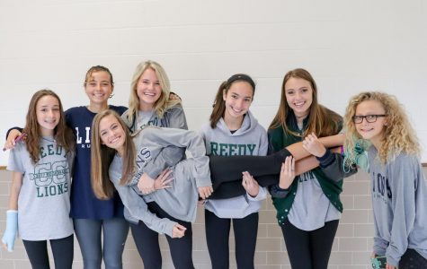 Varsity Cross Country holds freshman Colleen Steggman after the State Send Off in the hallways at Reedy.