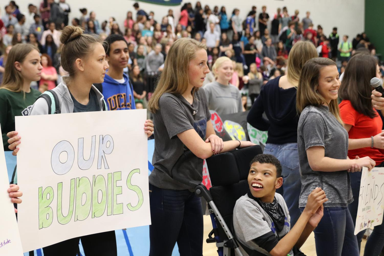 Senior Victoria Tamney and junior Grace Jensen with freshman Dominic Frezza tell the crowd what Best Buddies is thankful for at the Playoff pep rally, Nov. 17.